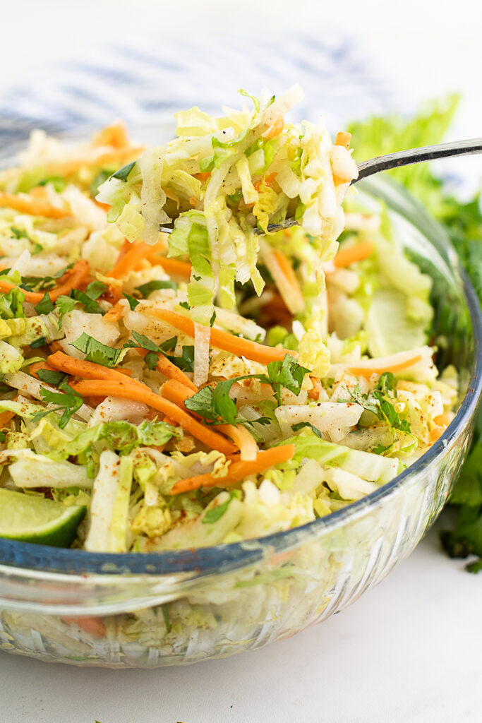 Large glass bowl filled with jicama slaw with a metal spoon taking a scoop out of it