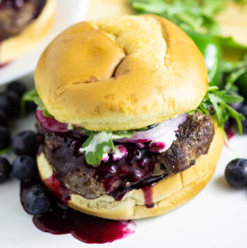 Spicy blueberry burger with blueberry sauce running down with fresh arugula and blueberries behind it